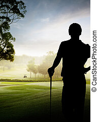 silhouette of golfer - silhouette of a golfer standing by...
