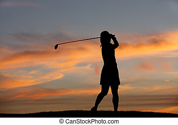 Silhouette of golfer swinging.
