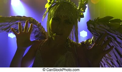 Silhouette of gorgeous woman in the image of the Greek goddess Artemis sings and dances on stage. Theatrical vocal dance show. Close up in slow motion