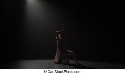 Silhouette of graceful girl dancing and sitting on splits at...