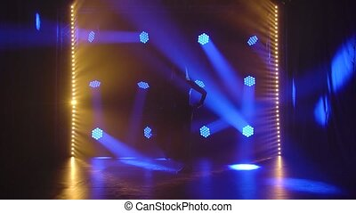 Silhouette of graceful slim woman dancing modern contemp choreography on a black background with blue lights. A charming dancer in a black suit performing acrobatic dance elements. Slow motion.