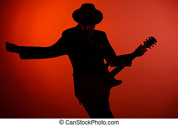 silhouette of guitarist on a red background.