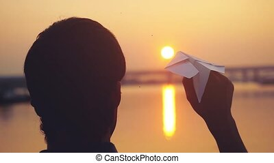 Silhouette of guy launch paper plane against the sea during sunset with sun flare and reflections in the water in slowmotion, as in childhood.