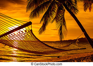 Silhouette of hammock and palm trees on a beach at sunset