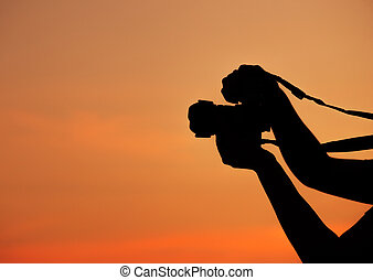 Silhouette of hand shooting with camera at sunset