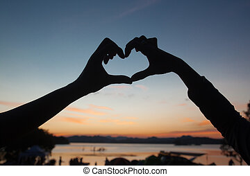 Silhouette of hand sign heart on twilight sky after sunset with the lake in background. Valentines and Love concept
