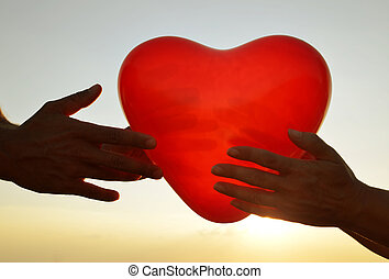 Silhouette of hands holding red balloon in the shape of heart.