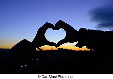 Silhouette of hands in form of heart when sweethearts have...