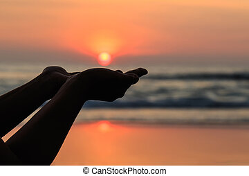 Silhouette of hands play with the sun at neach in sunset...