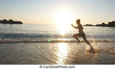 Silhouette of Happy Child is running on the beach at Sunset, raises splashes. Slow Motion