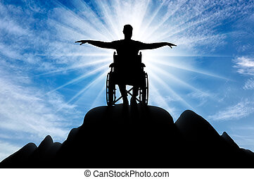Silhouette of happy disabled man in wheelchair on top of mountain