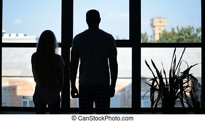 Silhouette of happy family embracing near window