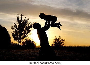 Silhouette of Happy Father Lifting Toddler Child in Air at Sunset