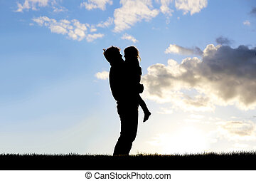 Silhouette of Happy Father Lovingly Hugging Little Child Outside at Sunset