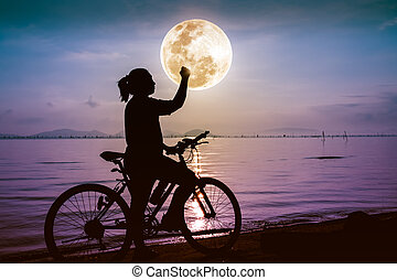 Silhouette of happy female celebrating with arm up towards the full moon. Suscess concept.