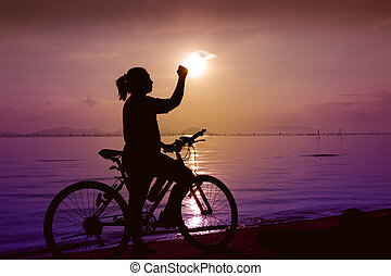Silhouette of happy female celebrating with arm up towards the sun. Suscess concept.