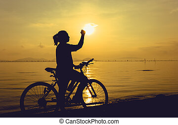Silhouette of happy female celebrating with arm up towards the sunset. Suscess concept.