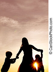 Silhouette of Happy Mother and Little Children Dancing Outside at Sunset