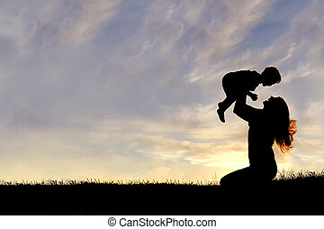 Silhouette of Happy Mother Playing Outside with Baby