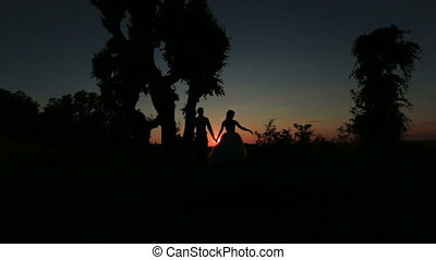 Silhouette of happy wedding couple softly kissing on the forest background. Wonderful sunset in countryside