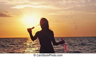 Silhouette of happy woman blowing soap bubbles on the beach at beautiful sunset in slwo motion. 1920x1080
