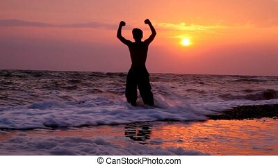 silhouette of happy young man with raised hands, sunset sea in background