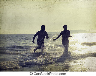 Silhouette of happy young teens playing on the beach