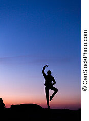 Silhouette of happy young woman against beautiful colorful sky.