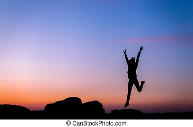 Silhouette of happy young woman jump against beautiful colorful