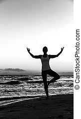 Silhouette of healthy woman in sportswear on seashore doing yoga