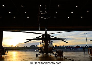 silhouette of helicopter in the hangar with sunrise background.