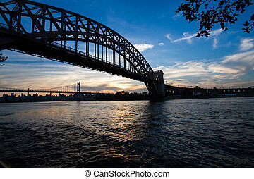 Silhouette of Hell Gate Bridge and Triborough bridge over the river, New York