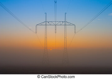 Silhouette of high voltage electrical pole structure at sunrise