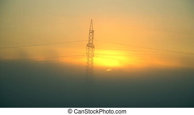 Silhouette of high voltage pole and many cables, electric...