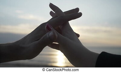 Silhouette of holding hands making heart shape with sunset...
