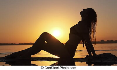 Silhouette of Hot Woman in Swimsuit Lying and Posing on Evening Beach at Sunset. Women's figure on the shore opposite Red Sun. Young woman relaxes by the river bank. Summer, Travel and Beauty concept