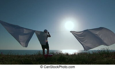 Silhouette of housewife and white laundry on a clothesline