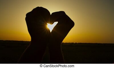 Silhouette of human hands in heart shape at sunset - ...