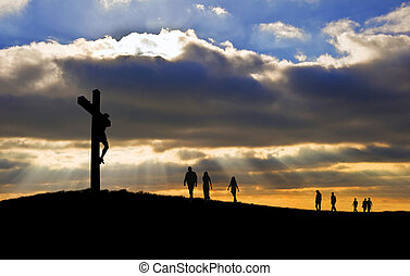Silhouette of Jesus Christ crucifixion on cross on Good Friday Easter witth people walking up hill towards Jesus