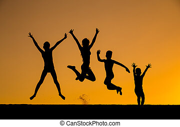 silhouette of jumping kids against sunset