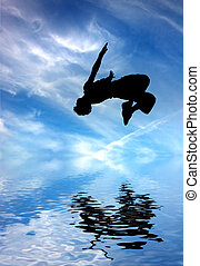 silhouette of jumping man against blue sky and clouds