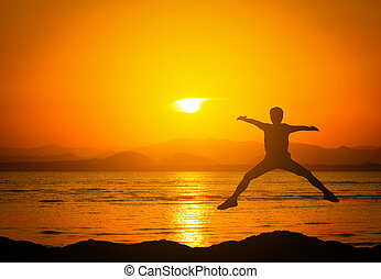 Silhouette of jumping man on mountains near the beach at sunset.