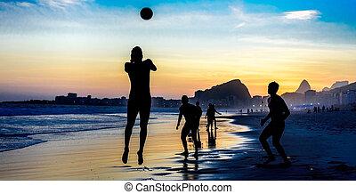 Silhouette of jumping man playing beach football on the background of beautiful sunset at Copacabana beach, Rio de Janeiro