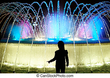 Silhouette of kid girl on colorful fountain