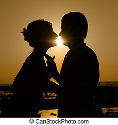Silhouette of kissing couple at sunset