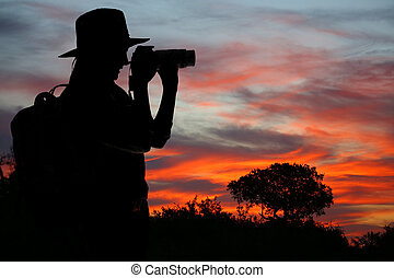 Silhouette of  Lady in Safari Dress taking Photographs at Sunset