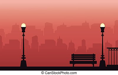 Silhouette of lamp and chair on street landscape at sunset