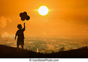 Silhouette of little boy hold bubble look at the sun , sunset background