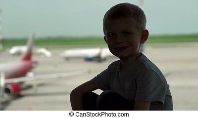 Silhouette of little boy near a window at the airport, he looks at the planes.