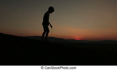 Silhouette of little boy playing with sand on the sunset